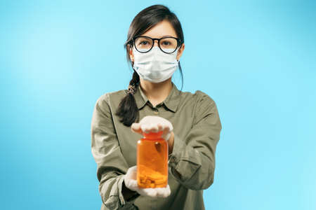 Portrait of a young woman in protective medical mask and gloves holding an orange bottle with pills or vitamins on a blue background. 版權商用圖片