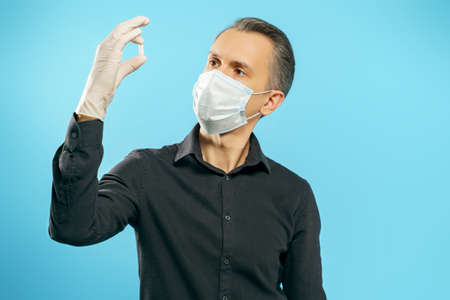 Young man in a protective medical mask and gloves holding a capsule or pill in his hands on a blue background. Healthcare and medicine concept