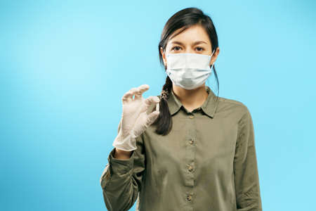 Portrait of a young woman in protective medical mask and gloves holding a capsule or pill on a blue background.