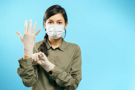 Portrait of a young woman in a medical mask putting on protective gloves on a blue background.