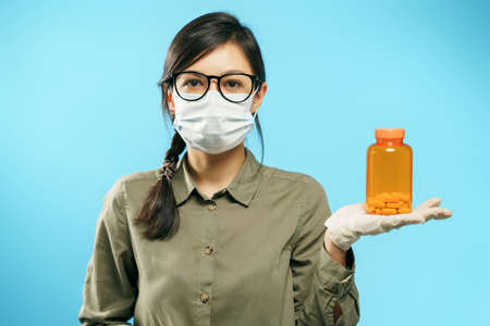 Portrait of a young woman in protective medical mask and gloves holding an orange bottle with pills or vitamins on a blue background