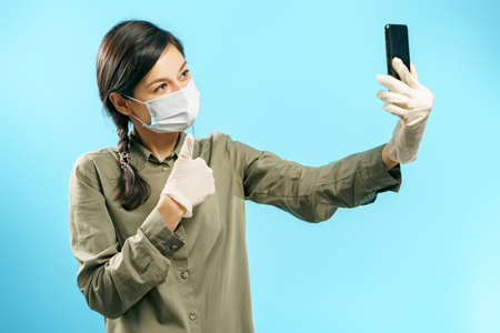 Young woman in protective medical mask and gloves making selfie or video call using smartphone showing thumb up on blue background.