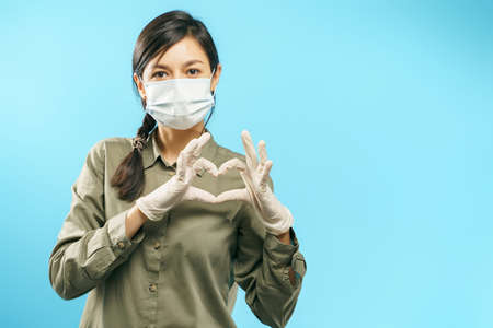 Portrait of a young woman with protective medical mask and gloves showing heart gesture on a blue background.