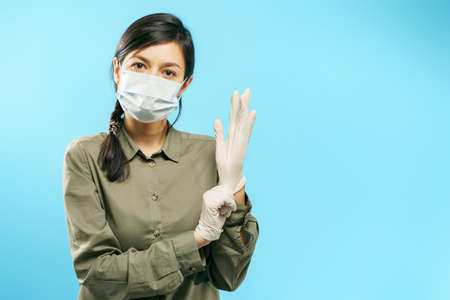Portrait of a young woman in a medical mask putting on protective gloves on a blue background