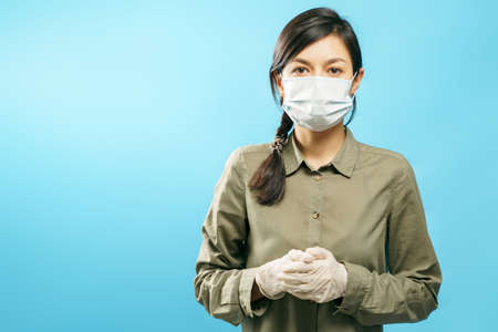 Portrait of a young woman in a protective medical mask and gloves on a blue background.