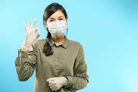 Portrait of young woman wearing a protective mask and gloves showing okay gesture on blue background. Coronavirus pandemic, dust allergy, protection against virus.