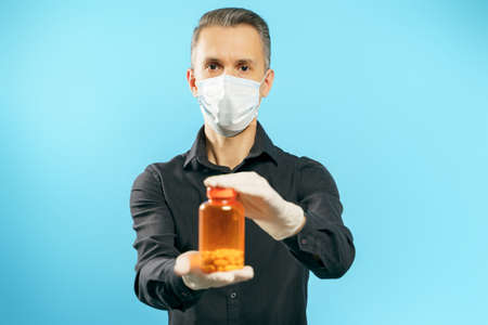 Portrait of a young man in protective medical mask and gloves holding an orange bottle with pills or vitamins on a blue background
