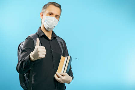 Portrait of a male student in a medical protective mask and gloves holding books and showing a thumbs up on a blue background