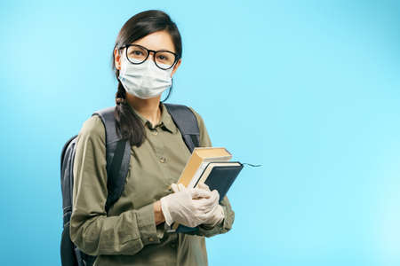 Portrait of a female student in a medical protective mask and gloves holding books on a blue background.