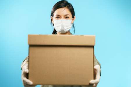 Close-up of a cardboard box in the hands of a young woman in a medical protective mask and gloves on a blue background. Secure delivery