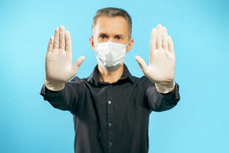 Close-up of the gloved hands of a young man in a medical protective mask on a blue background. Social distance. Stop gesture.