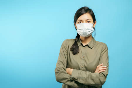 Portrait of a young woman in a protective medical mask with arms crossed on a blue background.