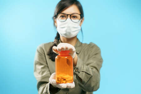 Close-up hands of a young woman in a medical protective mask and gloves holding an orange can with pills on a blue background. Prevention or treatment of virus and flu
