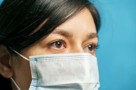 Close up portrait of a sad young asian woman in protective medical mask on a blue background. Fear and loneliness concept.