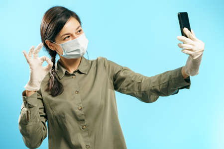 Young woman in protective medical mask and gloves making selfie or video call using smartphone and showing ok gesture on blue background. 版權商用圖片
