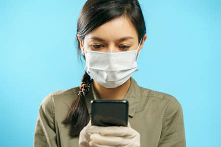 Young woman in protective medical mask and gloves using smartphone on a blue background. Online chat.