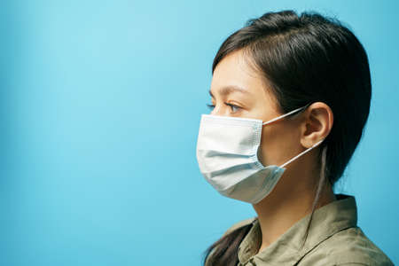 Close up portrait of a sad young asian woman in protective medical mask on a blue background. Fear and loneliness concept. Copy space