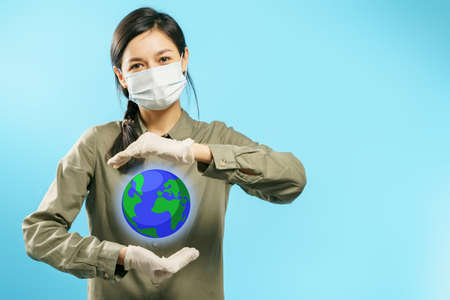 Portrait of a young woman in a protective medical mask and gloves holding a globe in his hands on a blue background. The concept of protecting the world from the coronovirus pandemic.