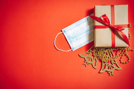Composition of Christmas decorations, a gift box in a ribbon and a protective medical mask on a red background.
