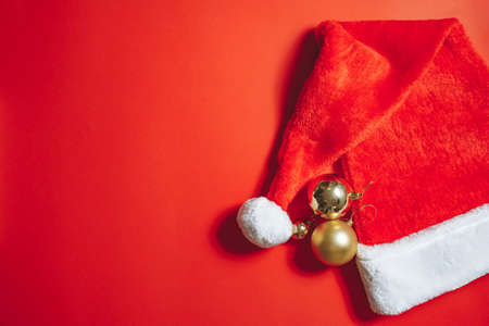 Close-up of santa hat and Christmas tree decorations on a red background. Copy space.