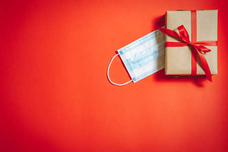 Gift box with ribbon and medical protective mask on red background. Copy space. 版權商用圖片