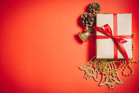 Christmas decorations and fir cones on a red background. Gift box wrapped in craft paper with a red ribbon. Xmas greeting card, banner.