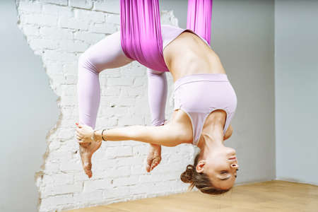Young woman doing stretching exercises using a hammock in a fitness studio. Aerial yoga.