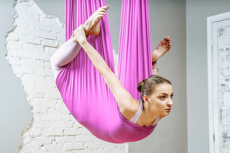 Young woman doing stretching exercises using a hammock in a fitness studio. Aerial yoga