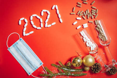 Composition of glasses with pills, Christmas decorations, fir sprigs and a medical mask on a red background. Top view. Copy space. 版權商用圖片