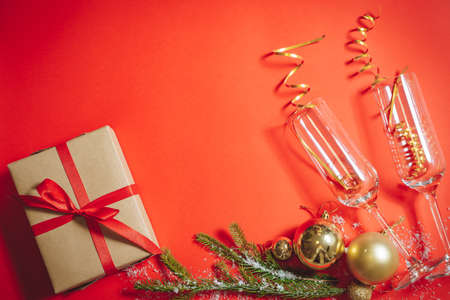 Composition of champagne glasses filled with serpentine, spruce branches, Christmas balls and gift box on a red background. Flat lay 版權商用圖片