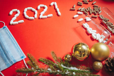 Composition of glasses with pills, Christmas decorations, fir sprigs and a medical mask on a red background. Copy space.