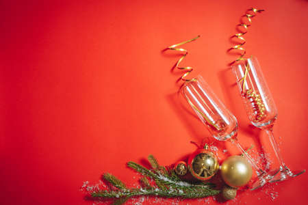 Composition of champagne glasses filled with serpentine, spruce branches and Christmas balls on a red background. Flat lay 版權商用圖片