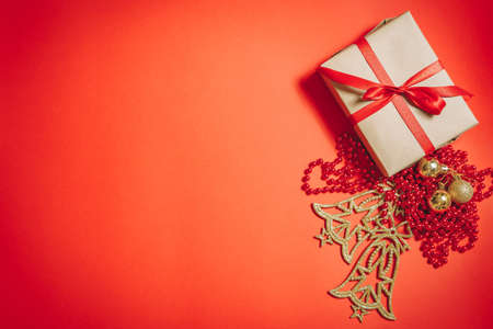 Christmas decorations and gift box in craft paper on a red background. Xmas greeting card, banner. Copy space. 版權商用圖片