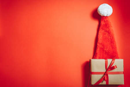 Santa hat and gift box wrapped in craft paper with ribbon on red background. Christmas concept.