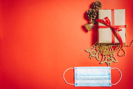 Composition of Christmas decorations, a gift box in a ribbon, fir cones and a protective medical mask on a red background.