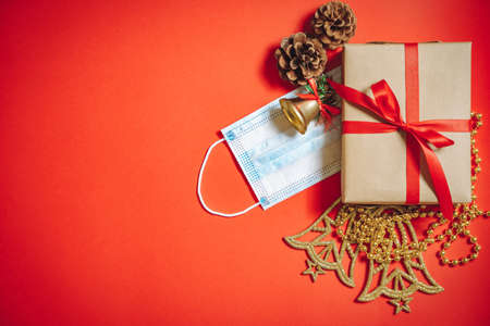Composition of Christmas decorations, a gift box in a ribbon, fir cones and a protective medical mask on a red background. Copy space.