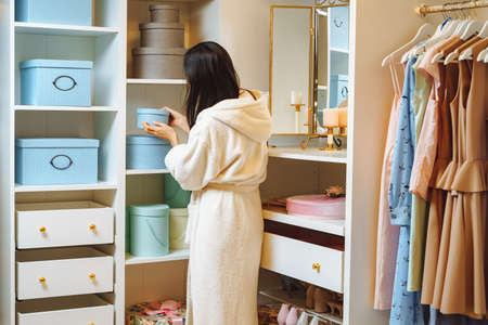 Young woman in a bathrobe taking a blue box from a wardrobe at home. Fashion and storage concept.