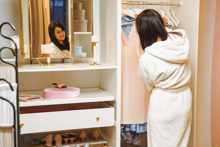 Attractive young woman in bathrobe choosing a dress in dressing room at home.