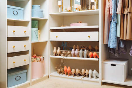 Large wardrobe with stylish women's clothing, shoes, accessories and boxes. Organization of storage space and fashion concept. 版權商用圖片