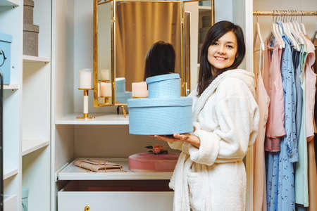 Happy young woman in bathrobe holding blue boxes and smiling in dressing room at home. Shopping and fashion concept.
