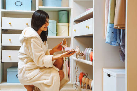 Attractive young woman in bathrobe choosing shoes in dressing room at home. 版權商用圖片