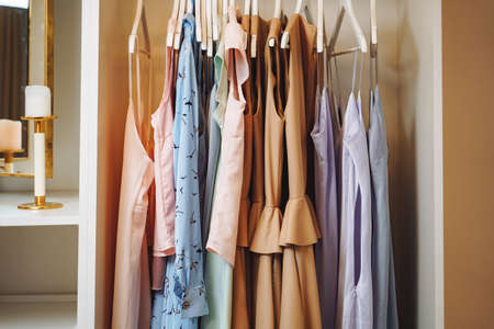 Women's clothing dresses and blouses on hangers in a dressing room or store