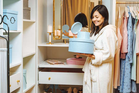 Smiling young woman in bathrobe opening blue box in dressing room at home. Shopping and fashion concept.