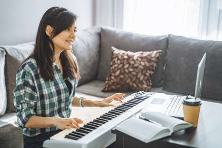 Young woman music teacher playing electric piano teaching remotely using laptop while working from home. Online education and leisure concept. 版權商用圖片