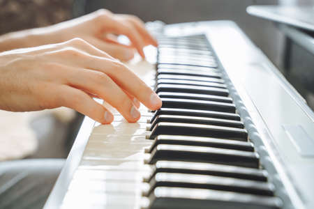 Close-up of male hands playing the electric piano. Background. 版權商用圖片