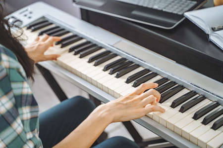 Close up of unrecognizable young woman playing electric piano teaching remotely using laptop while working from home. Online education and leisure concept. 版權商用圖片