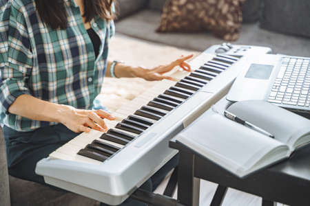 Close up of hands of unrecognizable young woman playing electric piano teaching remotely using laptop while working from home. Online education and leisure concept.