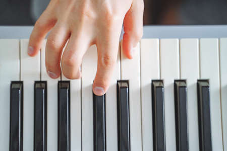 Close-up of male hand playing the electric piano. Background. Top view 版權商用圖片