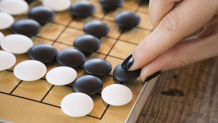 Close up view of female hand playing black and white stone pieces on Chinese go game board. Outside activity with natural sun light.