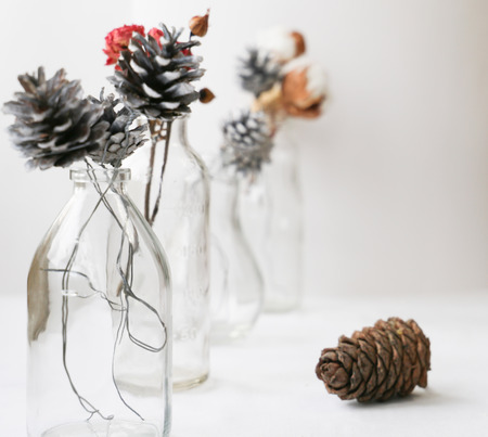 home decoration of glass bottles, Christmas tree cones and dried flowers on white table